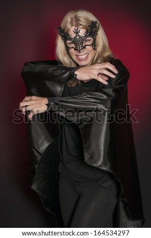 pretty woman dressed as Halloween vampire bat isolated on dark background #164534297