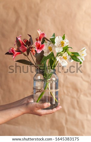 Unrecognizable woman hands holding up a glass jar full with easter eggs. Colorful spring flowers in the glass jar. Spring floral stock image