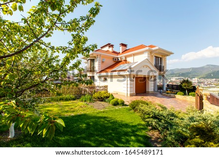 The facade of a classic Mediterranean two-storey cottage in the spring. The cottage is white with a red tiled roof. In front of the cottage there is a green lawn and flowering trees.  #1645489171