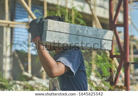 A man on a building construction site carries concrete blocks on his shoulder.   #1645625542