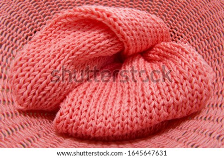 Knitted from a pink yarn sweater and thread for knitting closeup. Knitting as a hobby. Accessories for knitting. #1645647631