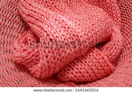 Knitted from a pink yarn sweater and thread for knitting closeup. Knitting as a hobby. Accessories for knitting. #1645665016