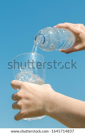 Puring drinking water on natural blue sky. #1645714837