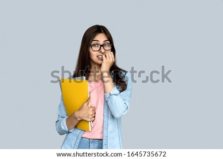 Scared stressed young indian student teen girl standing isolated on grey background with copy space, looking at camera feel fear nervous afraid of test exam and holding copybook in hand