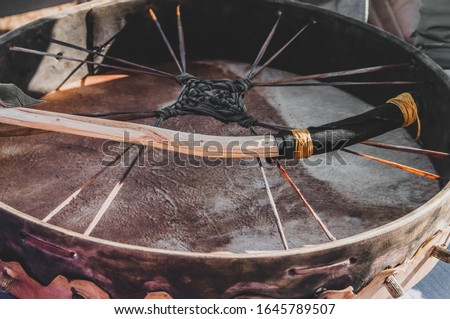 Closeup detail of a shamanic spiritual meditation ritual drum with a natural handmade wild wood branch drumstick  for a shamanism ceremony- Concept of mystical paganism or alternative lifestyle #1645789507