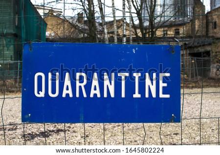 Blue warning sign on a fence - Quarantine. Warning about epidemic quarantine. Coronavirus disease. nCoV alert sign. Biohazard, not trans-passing. Blue sign handing on a fence. Sign on wire fence. #1645802224