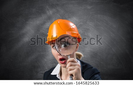 Building inspector looking through magnifying glass. Young construction specialist in safety helmet with magnifier on grey wall background. Consultancy and expertise. Professional valuation services #1645825633