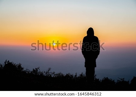 An Asian man standing alone alone near a cliff to watch the sunrise. Silhouette concept  #1645846312