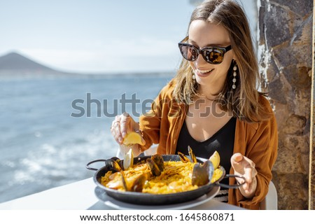 Woman eating paella, traditional spanish dish, while sitting at the restaurant terrace near the ocean. Concept of sea food and good summer vacations #1645860871