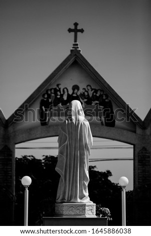 Black and white concept photo .Outdoor behind statue of Jesus with  cross symbol