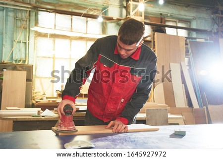 Process of production and manufacture of wooden furniture in furniture factory. Worker carpenter man in overalls processes wood on special equipment #1645927972