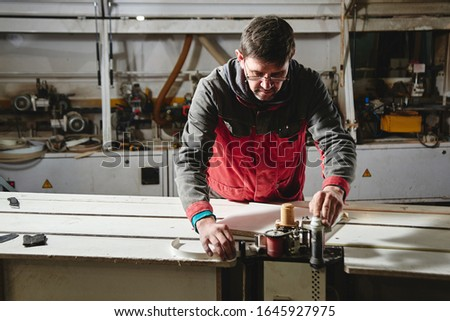 Process of production and manufacture of wooden furniture in furniture factory. Worker carpenter man in overalls processes wood on special equipment #1645927975