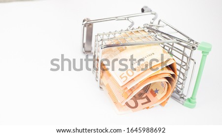 The concept of buying currency. Buying Euros. Metal cart with euro banknotes on a white background. close up. #1645988692