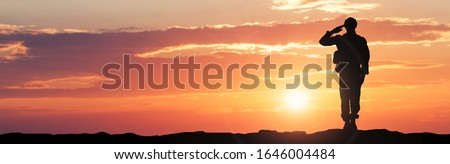 Silhouette Of A Soldier Saluting During Sunset Royalty-Free Stock Photo #1646004484