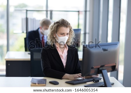 Business woman with curly blonde hair wearing a mask sitting in office, Concept,contagious disease, covid 19, coronavirus. Royalty-Free Stock Photo #1646005354