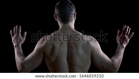 a brunette with pale skin poses with his back against a black background. he raises open palms to shoulder level and turns them, then head. the man turns and makes undulating movements with hands #1646059210