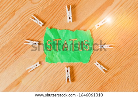 Text sign showing Status. Conceptual photo situation at a particular time during a process Professional position Colored clothespin papers empty reminder wooden floor background office. #1646061010