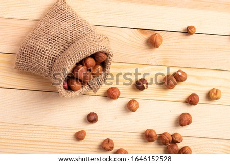 organic heap of hazelnuts in burlap bag on a old wooden table #1646152528