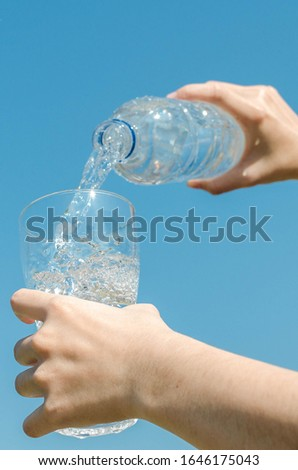 Puring drinking water on natural blue sky. #1646175043