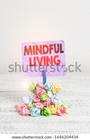Writing note showing Mindful Living. Business photo showcasing Having a sense of purpose and setting goals in life Reminder pile colored crumpled paper clothespin wooden space. #1646204434