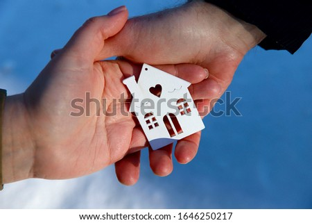 Two hands hold a mock up of a house. A man and a woman hold hands. A happy married couple hold a toy in the shape of a house. Close-up, side view, free space.