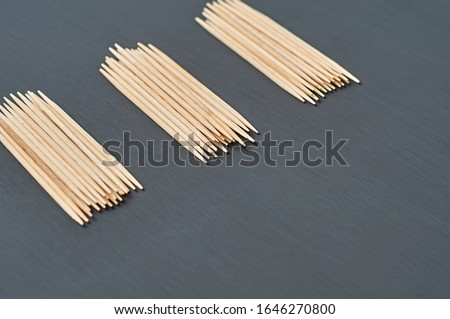 Three heaps of wooden toothpicks lies on black concrete desk on kitchen. Space for text #1646270800