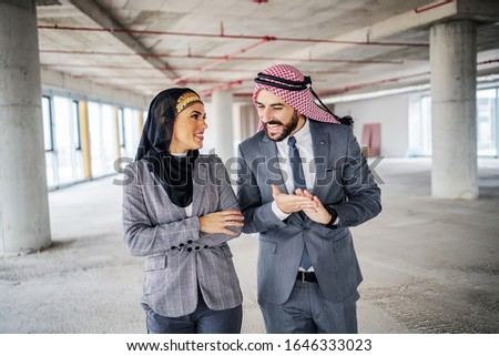 Satisfied muslim investors standing in building in construction process and talking about price for that place. Money is never a problem if plan they have is going well. #1646333023