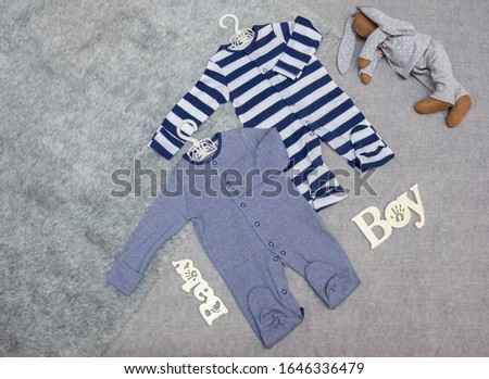 Bodysuits, clothes on a newborn baby boy. bodysuits on a gray background with place for text #1646336479
