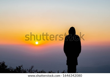 An Asian man standing alone alone near a cliff to watch the sunrise. Silhouette concept - Image #1646342080
