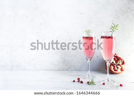 Mimosa cocktail with Rose Champagne, Pomegranate and Rosemary in flute glasses,  copy space. Mocktail, Mimosa sparkling pink drink. #1646344666