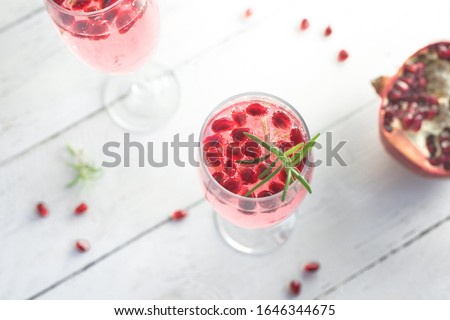 Mimosa cocktail with Rose Champagne, Pomegranate and Rosemary in flute glasses,  close up. Mocktail, Mimosa sparkling pink drink. #1646344675