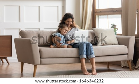 Full length attractive young mommy embracing small preschool daughter, making purchases in internet store, shopping online in living room. Happy family of two watching comedy movie cartoons on laptop.