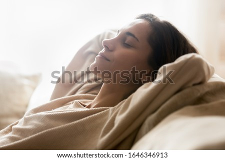 Smiling young woman lying on comfortable couch hands over head relaxing on sunny weekend at home, happy calm millennial girl rest on sofa in living room, breathe fresh air, stress free concept Royalty-Free Stock Photo #1646346913