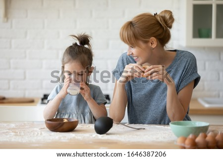 Happy young Caucasian mother and little preschooler daughter sit at kitchen table baking eating cookies together, smiling mom have fun with small girl child teach bakery enjoy family weekend at home #1646387206