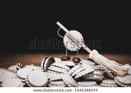 Crown cork or bottle cap miniature figures sweeping other caps with a sweeper, funny conceptual scene for beverages and drinks #1646388694