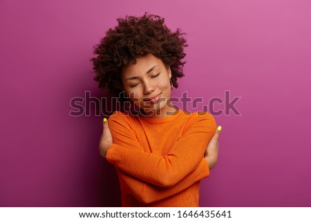 Lovely pretty woman embraces herself, feels good, comfortable and fullfilled, has high self esteem, tilts head and closes eyes, being egoisitc person, wears orange jumper isolated on purple background #1646435641