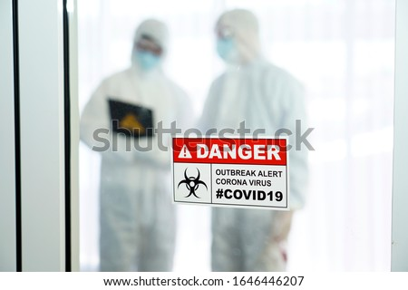 Outbreak alert Coronavirus COVID 19, COVID 19 signage in front of control area with doctors in personal protective equipment inside. #1646446207