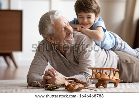 Happy little schoolboy lying on older senior grandfather on floor carpet, having fun together in living room. Joyful different generations family playing, enjoying free weekend time at home. Royalty-Free Stock Photo #1646468788