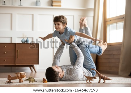 Joyful young man father lying on carpet floor, lifting excited happy little child son at home. Full length carefree two generations family having fun, practicing acroyoga in pair in living room. Royalty-Free Stock Photo #1646469193