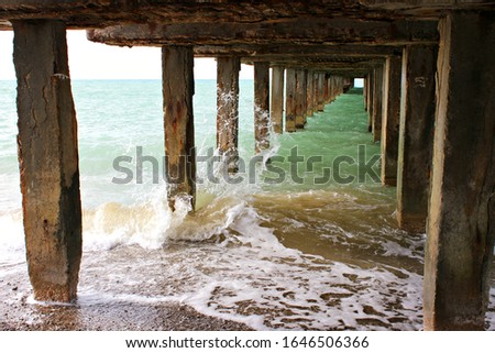 Underneath a fishing pier. the support of the sea promenade, under the bridge, the sea water under the pier #1646506366