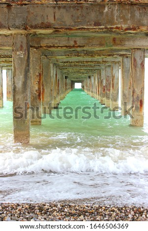 Underneath a fishing pier. the support of the sea promenade, under the bridge, the sea water under the pier #1646506369