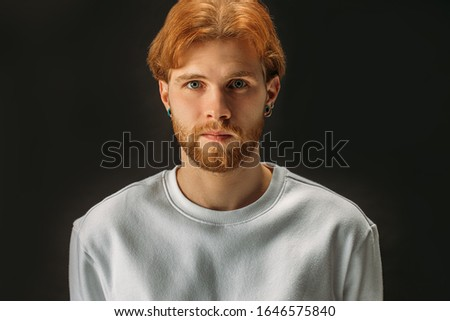 confident, serious redhead guy isolated over black background. young caucasian bearded man with unique apperance seriously look at camera, wearing white clothes. people concept, people diversity #1646575840