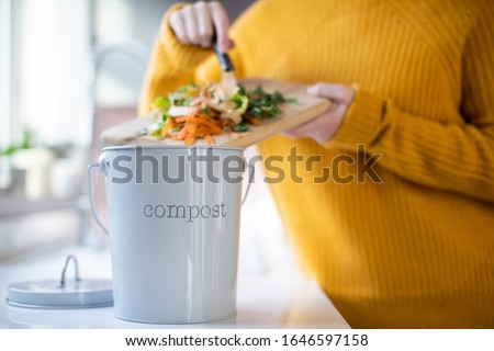 Close Up Of Woman Making Compost From Vegetable Leftovers In Kitchen #1646597158