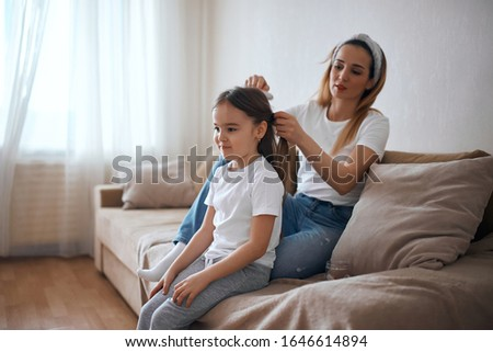 Mommy brushing her little daughter's hair in baedroom, preparing her to a kindergarden, school. close up photo.