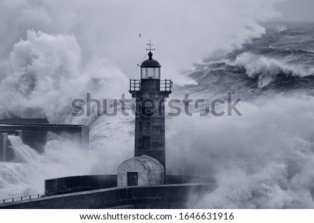Storm at sea. Douro river old pier and lighthouse. Focus on the lighthouse and foreground. Converted black and white. Toned blue.