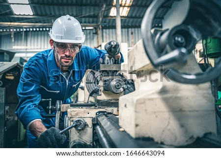 Male worker in blue jumpsuit and white hardhat operating lathe machine.  Royalty-Free Stock Photo #1646643094