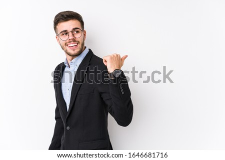Young caucasian business man posing in a white background isolated Young caucasian business man points with thumb finger away, laughing and carefree. #1646681716