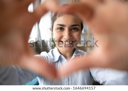 Portrait of overjoyed millennial Indian girl have fun make heart with hands posing in living room, profile picture of happy young ethnic woman look at camera smiling relaxing on weekend at home