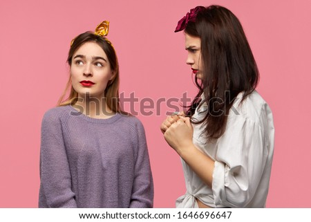 Stylish young female shaking fists, threatening her friend who is looking up with careless facial expression as if ignoring menace from her. Angry displeased woman expressing negative emotions #1646696647