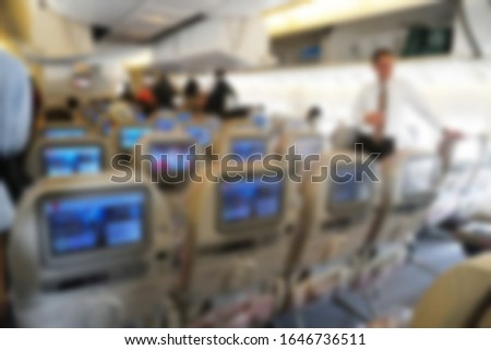 Interior of airplane with passengers sitting on seats some passenger putting bag on top shelf cabin. Travel concept with copy space blur picture for background